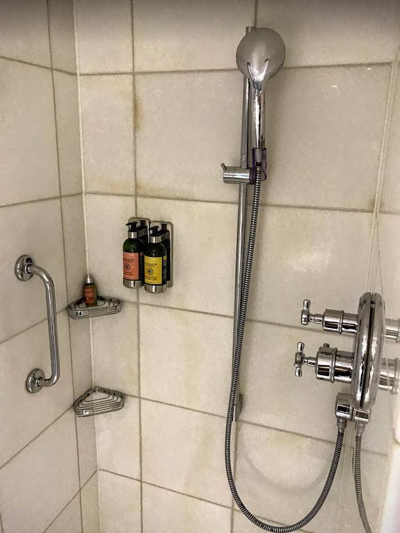 浴室只有淋浴間,大理石牆面已經可以看到歲月留下的痕跡